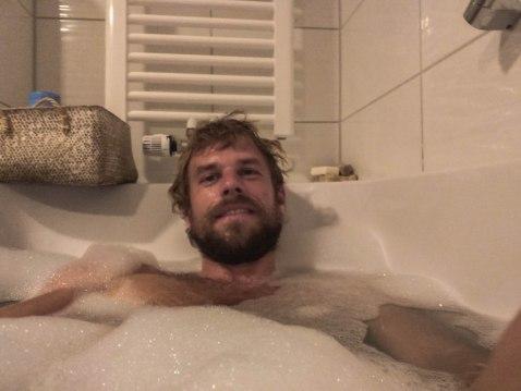 A blonde man taking a bath at home