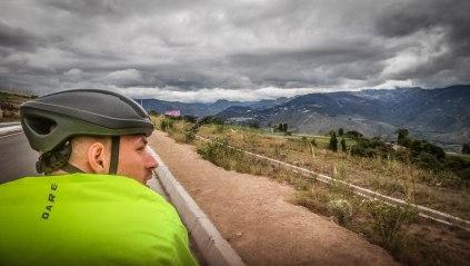 back view of a man cycling through the countryside of Ecuador