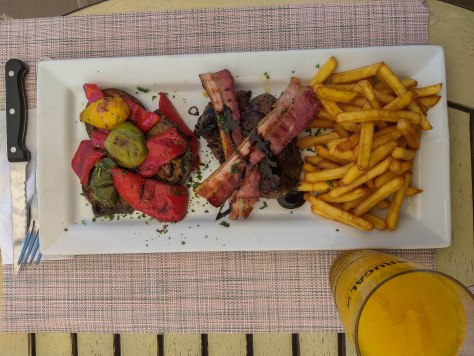 meat dish with french fries, vegetables and a juice