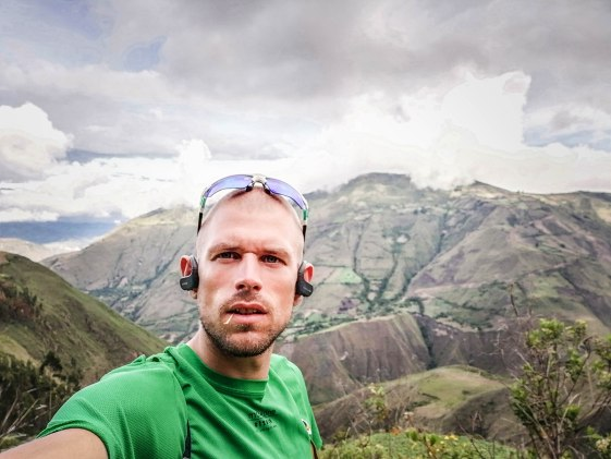 A bearded German backpacker wearing sunglasses and a green T-shirt off-the-grid hiking in the mountain in Ecuador