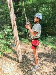 man setting up his climbing gear in the Fun Forest Kandel