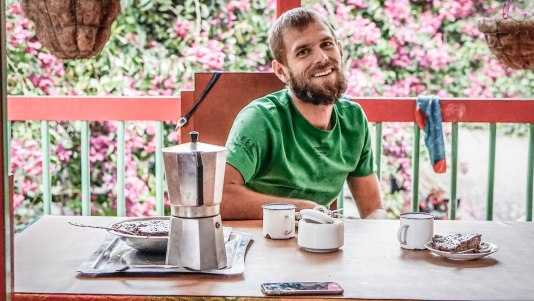 A man wearing a green T-shirt having cafe on a table in Colombia