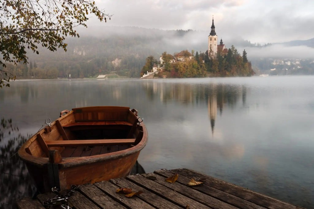 wooden boat across a lake from a distant castle on a cloudy day
