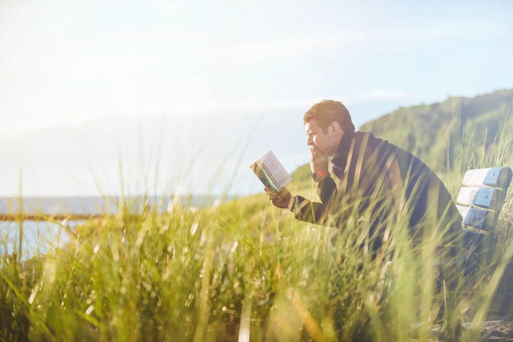 A man making time to read while sitting on a bench in the crass looking out across a lake.