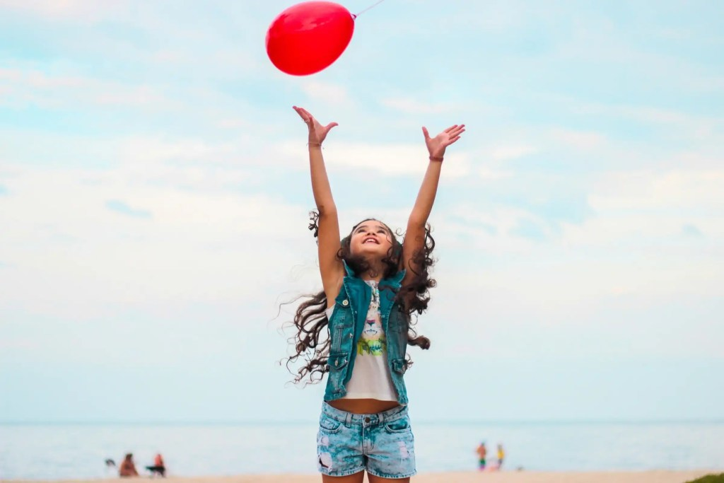 A little girl at a beach reaching her hands up for a red helium balloon above here, objectifying how we can all positively influence our children.