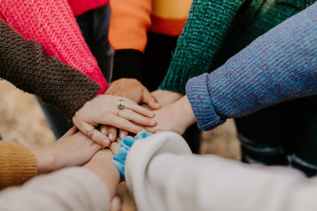 Several pairs of hands placed over each other prior to a team cheer.
