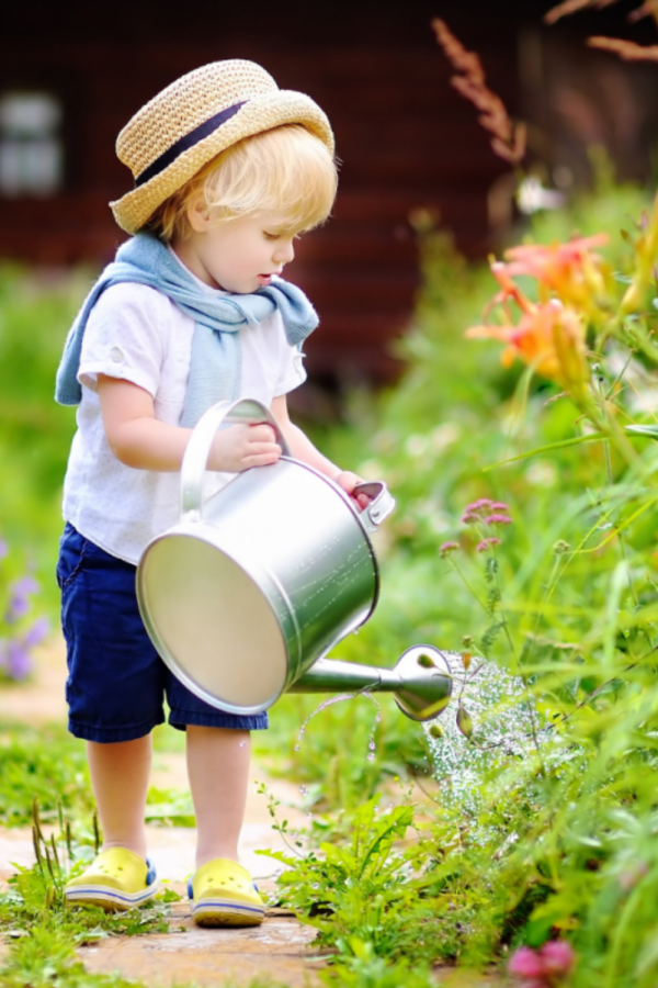 handsome little boy with hat watering the flowers on a summer day