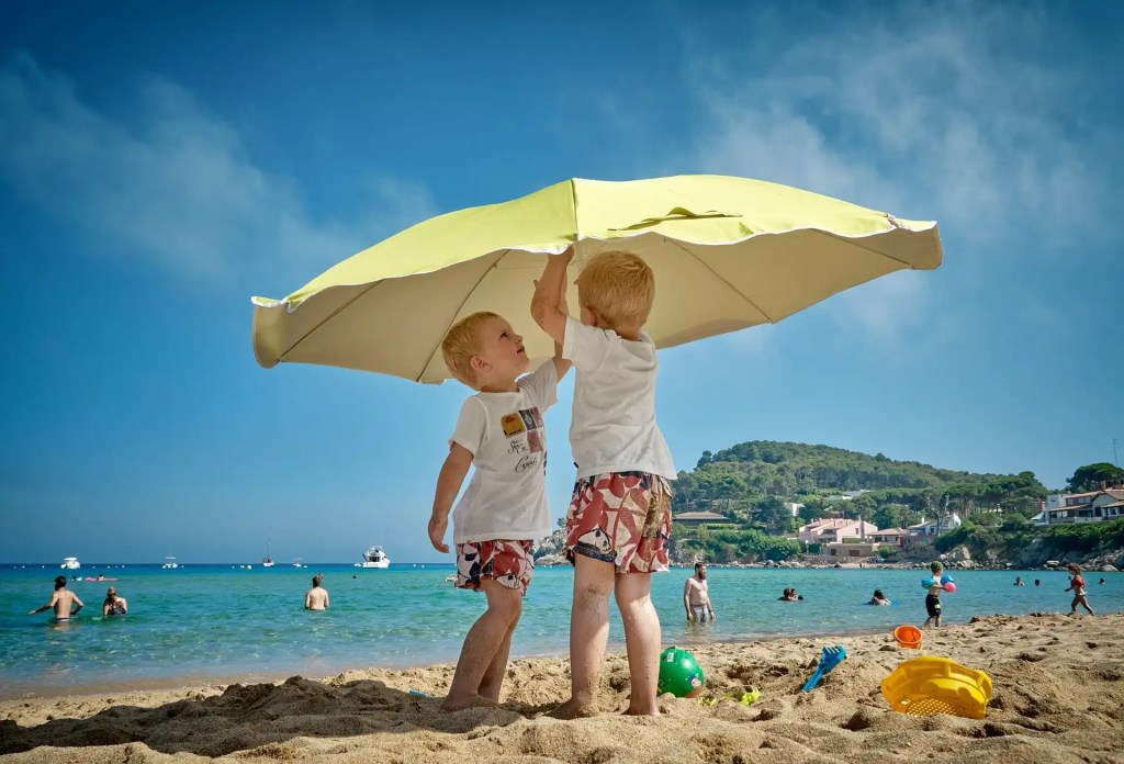 Two boys put up an umbrella on the beach while their parents relax in the ocean on a wallet-friendly family vacation.