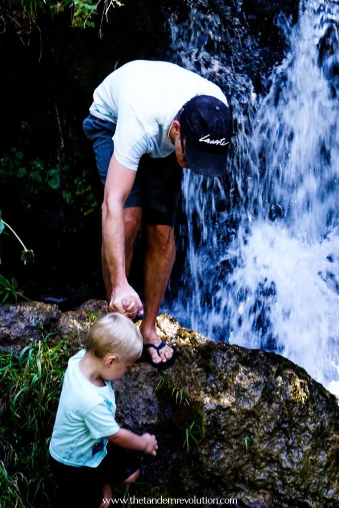 Father helping son climb on a rock near a waterfall