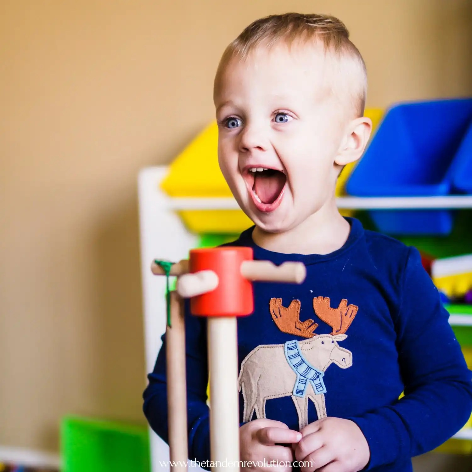 Happy toddler with a big smile on his face playing with toys
