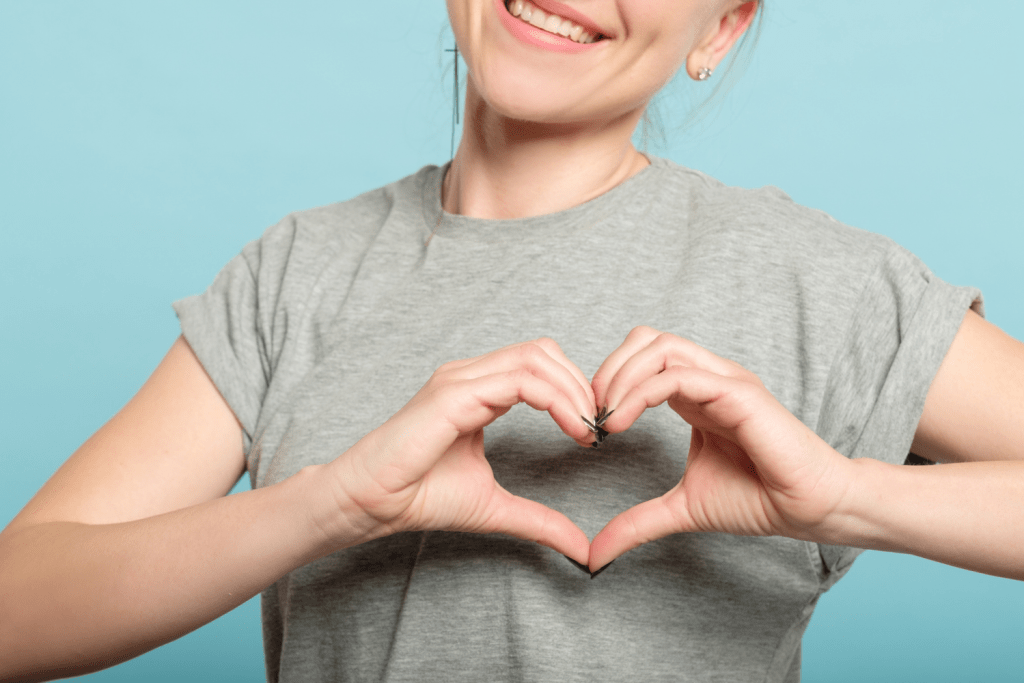 A woman makes a heart sign with her hands, showing gratitude to increase positivity in her relationship.