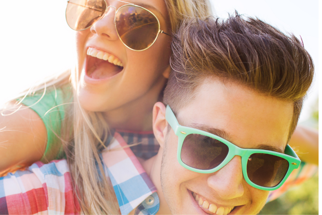 A husband and wife in sun glasses have fun while taking a selfie together.