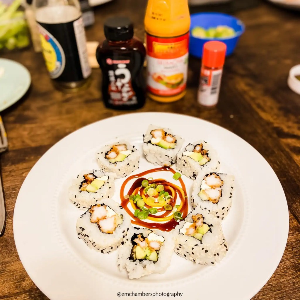 A picture of homemade sushi on a white plate with condiments and sauce