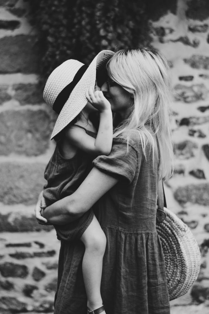 A mom holding and staring into the eyes of her daughter who is wearing a sun hat
