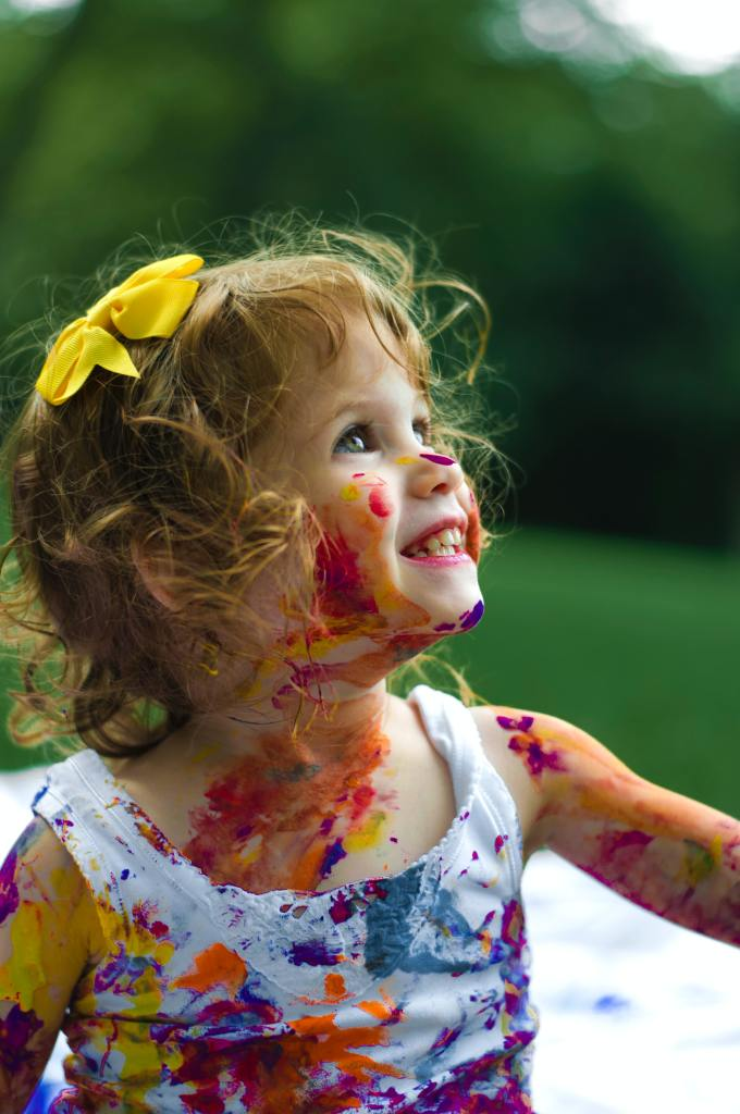 Young girl smiling with a yellow bow in her hair and paint on her face and dress