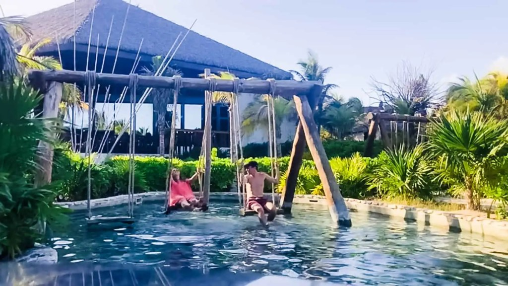 Husband and wife sitting on swings over a clear pool next to palm trees