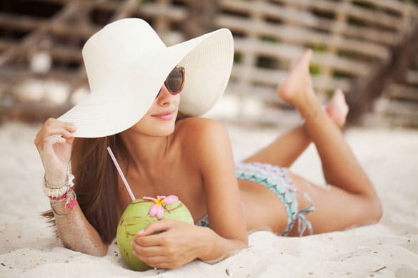 Beautiful-woman-relaxing-on-a-paradise-beach-with-coconut