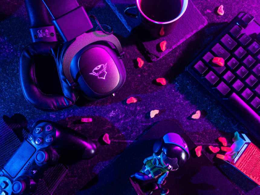 Headphones, keyboard, coffee, snacks, and controllers lay strewn after a hard gaming session.