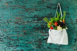 Market fresh salad vegetables hanging in a natural cotton recyclable shopping bag by a hook on a wooden turquoise coloured wall.