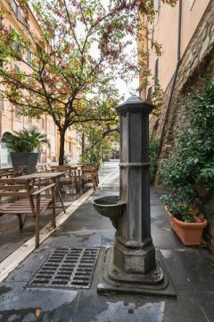 Antique drinking fountain in old town Civitavecchia, Italy.