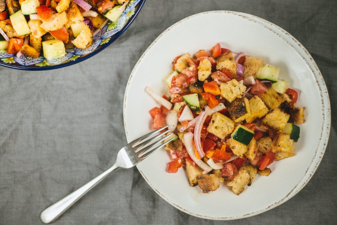 we toss cucumber, bread, tomatoes, and purple onion for the pazanella salad recipe by The Taste Edit