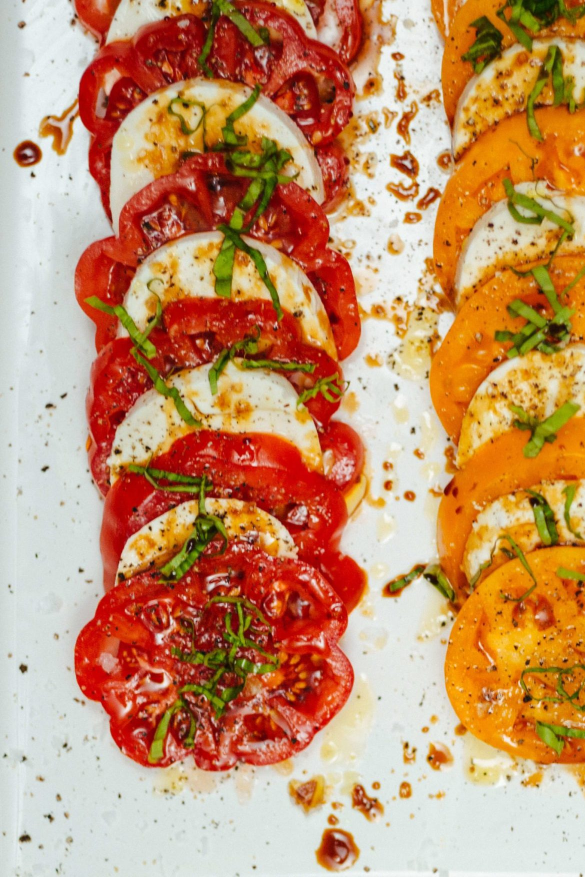 Caprese salad on a white dish with heirloom tomatoes