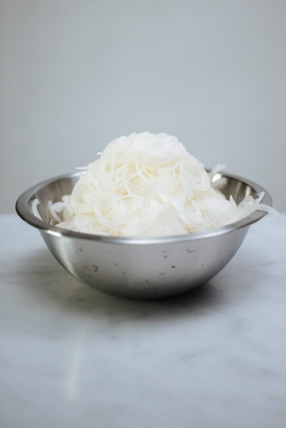 A bowl full of sliced onions for french onion soup