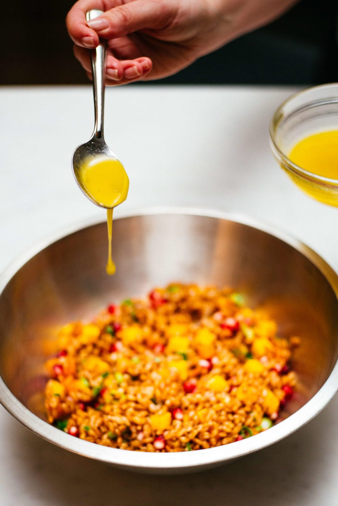 Adding the olive oil dressing to this farro salad