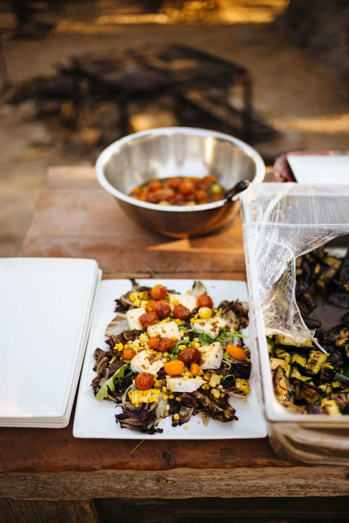 Greg Denton and Gabrielle Quiñónez-Denton make their Grilled Radicchio and corn salad with Mt Tam triple cream and roasted tomato vinaigrette at The Resort at Paws Up Cookbook Live during the chuckwagon, The Taste Edit