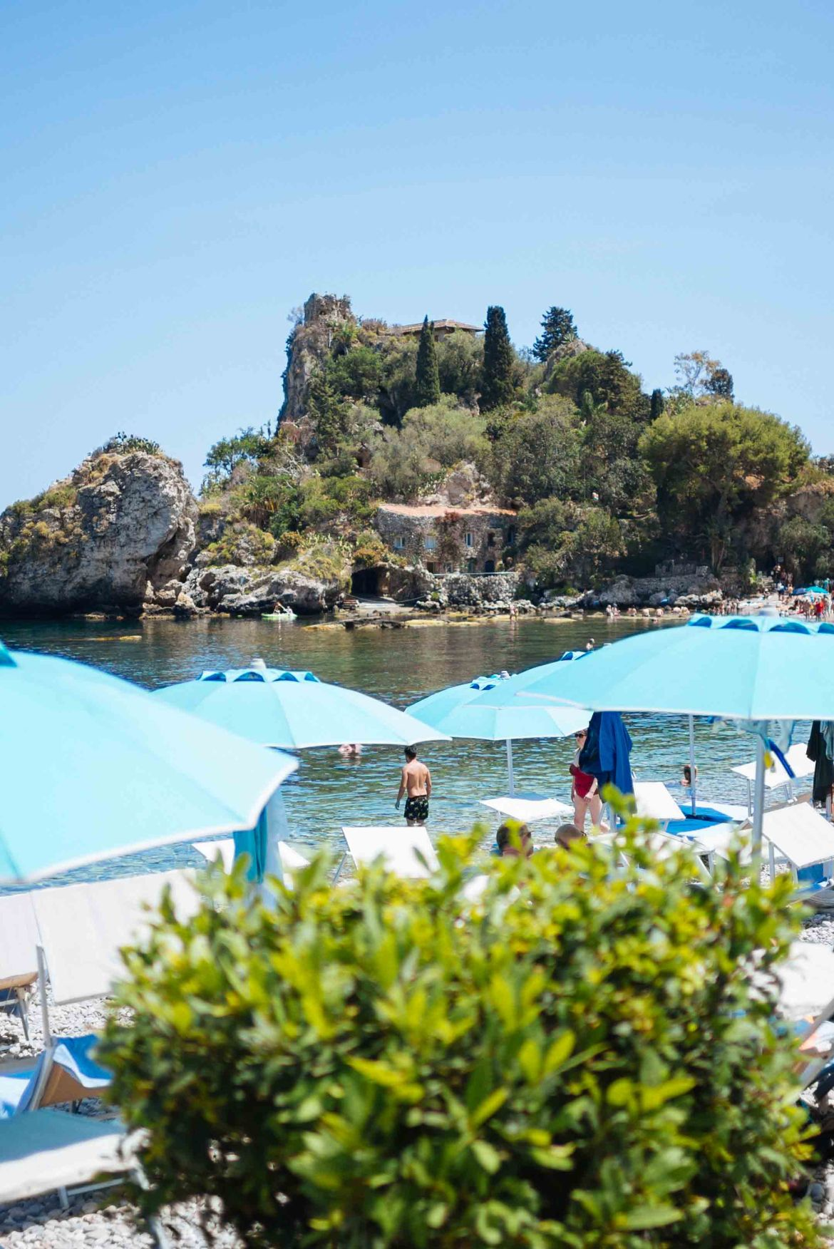 Sit along the water in Sicily at the beach of Isola Bella