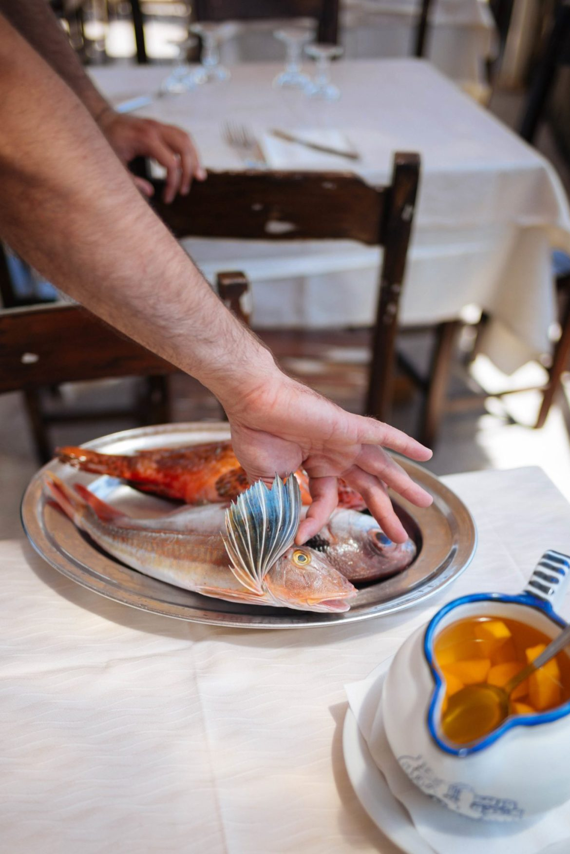 A waiter in Ischia, Italy shows us the different fish on the fish-of-the-day platter. The fish is caught that morning and can be prepared various ways, like the best fish pasta recipe that we've perfected for easy fish dinners. #pasta #fish #italy #recipe