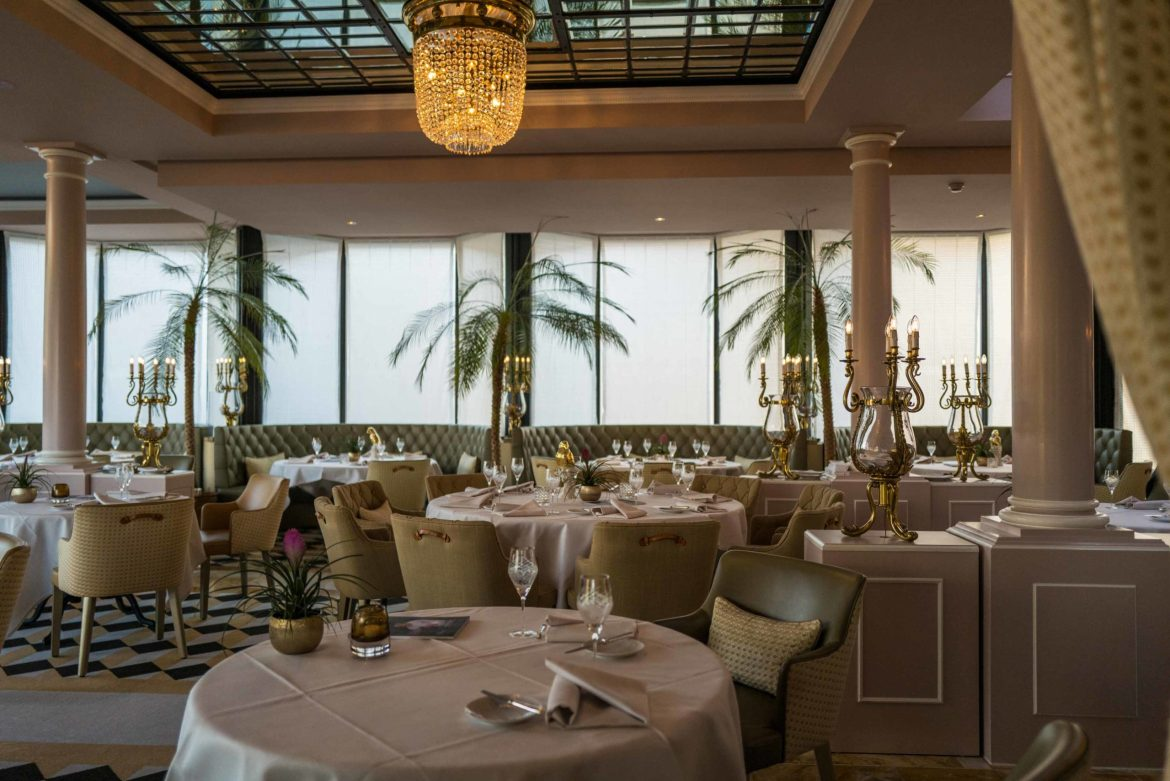 Book a table at La Terrasse restaurant at the Victoria Jungfrau lthat feels like you're in southern France filled with palm trees and beautiful decor #decor #restaurant #palmtree