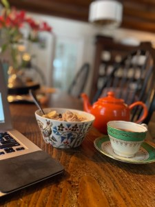 A teacup and teapot in a cozy-looking setting