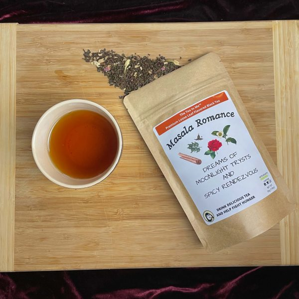 A cup of The Tea In Me Masala Romance tea with the bag and loose tea leaves.