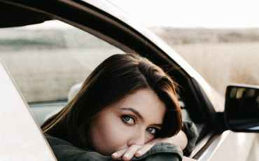 pensive woman sitting in car and looking at camera