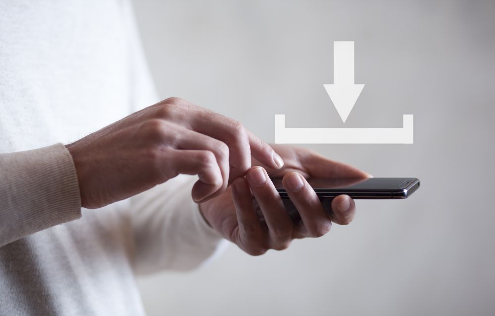 Download concept above a smartphone held by a man