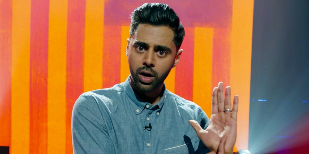 """Hasan Minhaj in standing in front of a colorful screen during """"Homecoming King."""""""