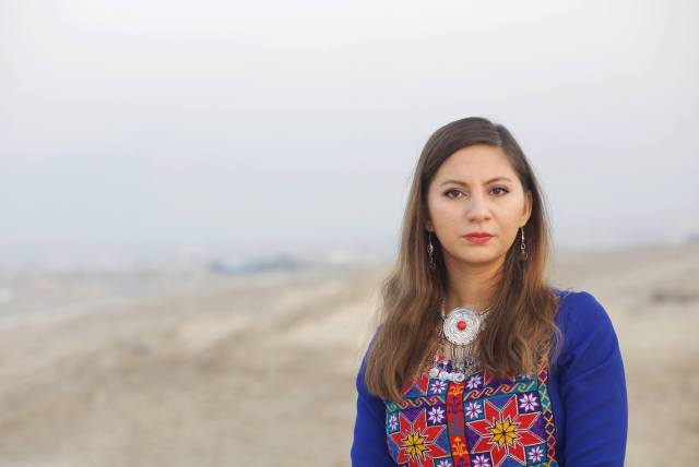 NoorJahan Akbar is standing in a desert, facing the camera wearing a bright blue Afghan dress with beautiful red, yellow and green embroidery.