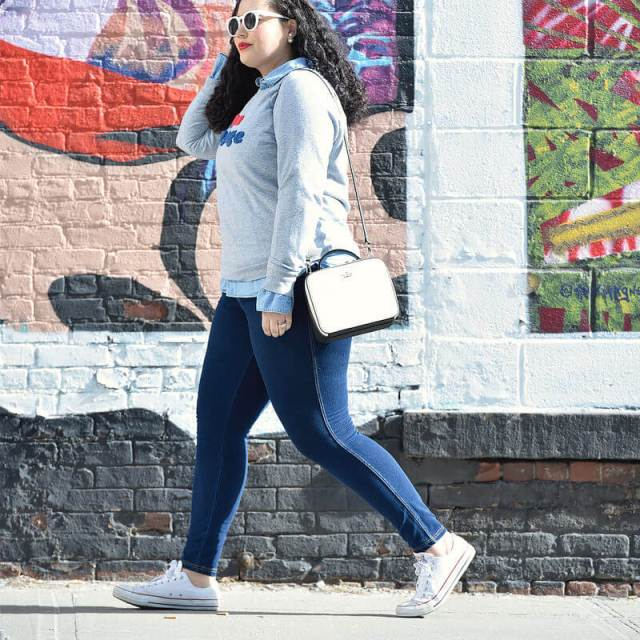 Image shows Tanesha Aswathi is walking alongside a mural, she is dressed in jeans, a stylish sweatshirt and a purse.