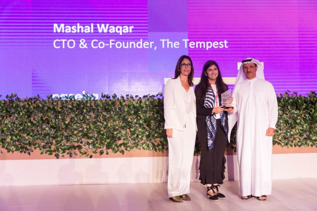 Mashal Waqar holding award, standing between Sophie Le Ray and H.E. Sultan bin Saeed Al Mansoori on stage. They are facing the audience. Purple screen in the background with text Young Leader of The Year and Mashal Waqar CTO and Cofounder The Tempest.