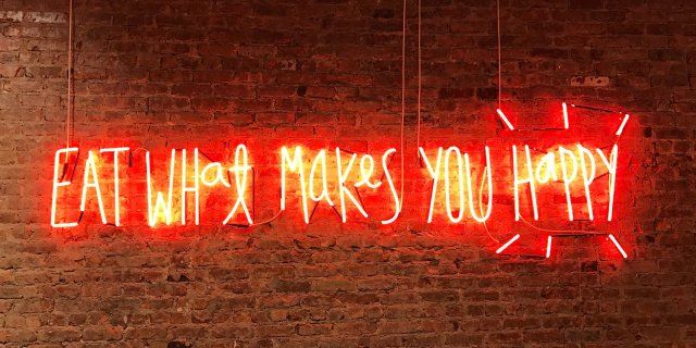 A neon sign reading 'eat what makes you happy'