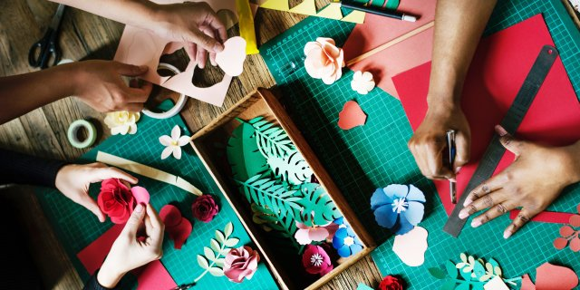 A flatlay of a craft table. Three people are crafting with paper and colorful embellishments.