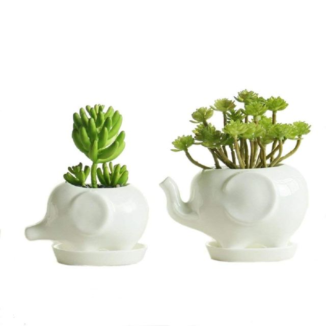 Image description: two all white elephant-shaped planters, each holding a green plant.