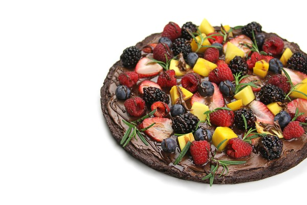 "Image description: a round brownie ""pizza"" covered in fruit toppings including strawberries, blueberries, raspberries, and mango chunks via"