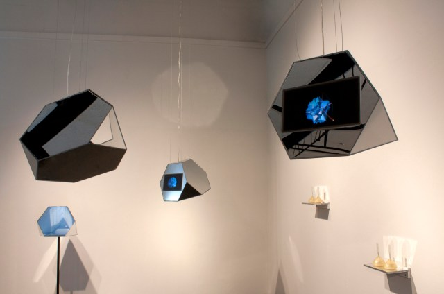 Photo from artist Cristina Molina's website [image description: mirrored crystalline orbs hang with small video screens hang from the ceiling of a gallery]