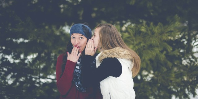 A girl sharing a secret with her friend.