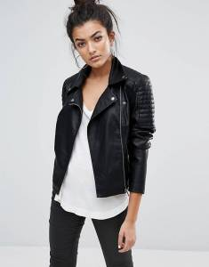 A woman wearing a leather jacket, white shirt and black pants.