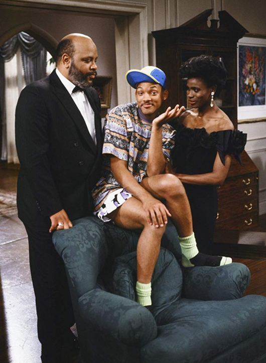 Will Smith from The Fresh Prince of Belair sits on the top of a chair, with his feet, in socks and sandals, on the seat of the chair. He wears a blue and yellow baseball hat, a long t-shirt with an abstract print and looks amused. On his left is his uncle and on his right his aunt, looking at him with a mixture of love and annoyance. They are both dressed fancy