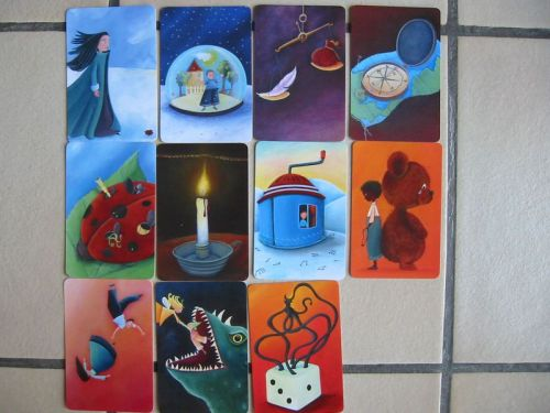 A collection of cards laid out on a tile floor from the board game Dixit featuring surrealist-style illustrations
