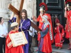Jesus emerges from the church with his cross